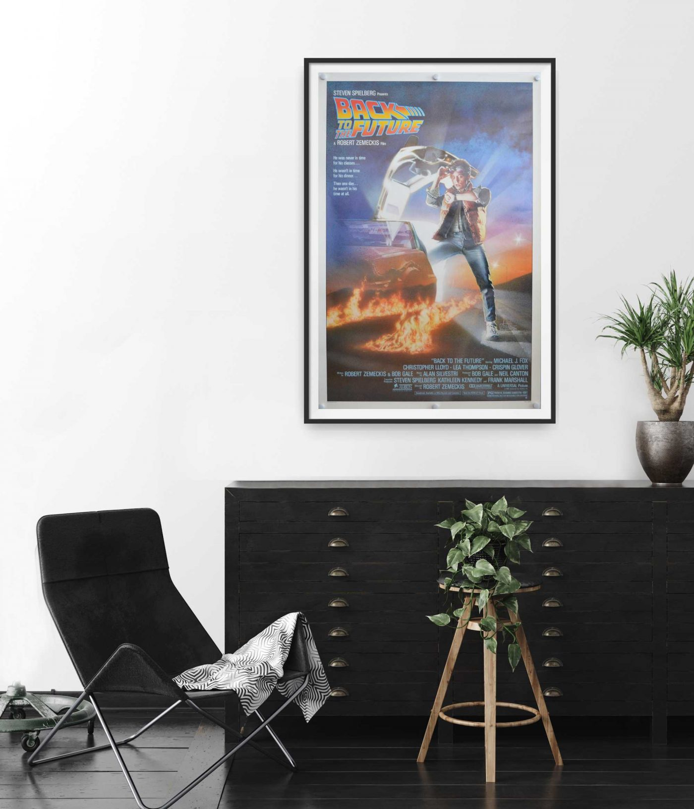 This is an original US cinema Poster for the Film 'Back to the Future'. The poster shows Marty McFly (played by Michael J Fox) standing beside the time travelling DeLorean car.