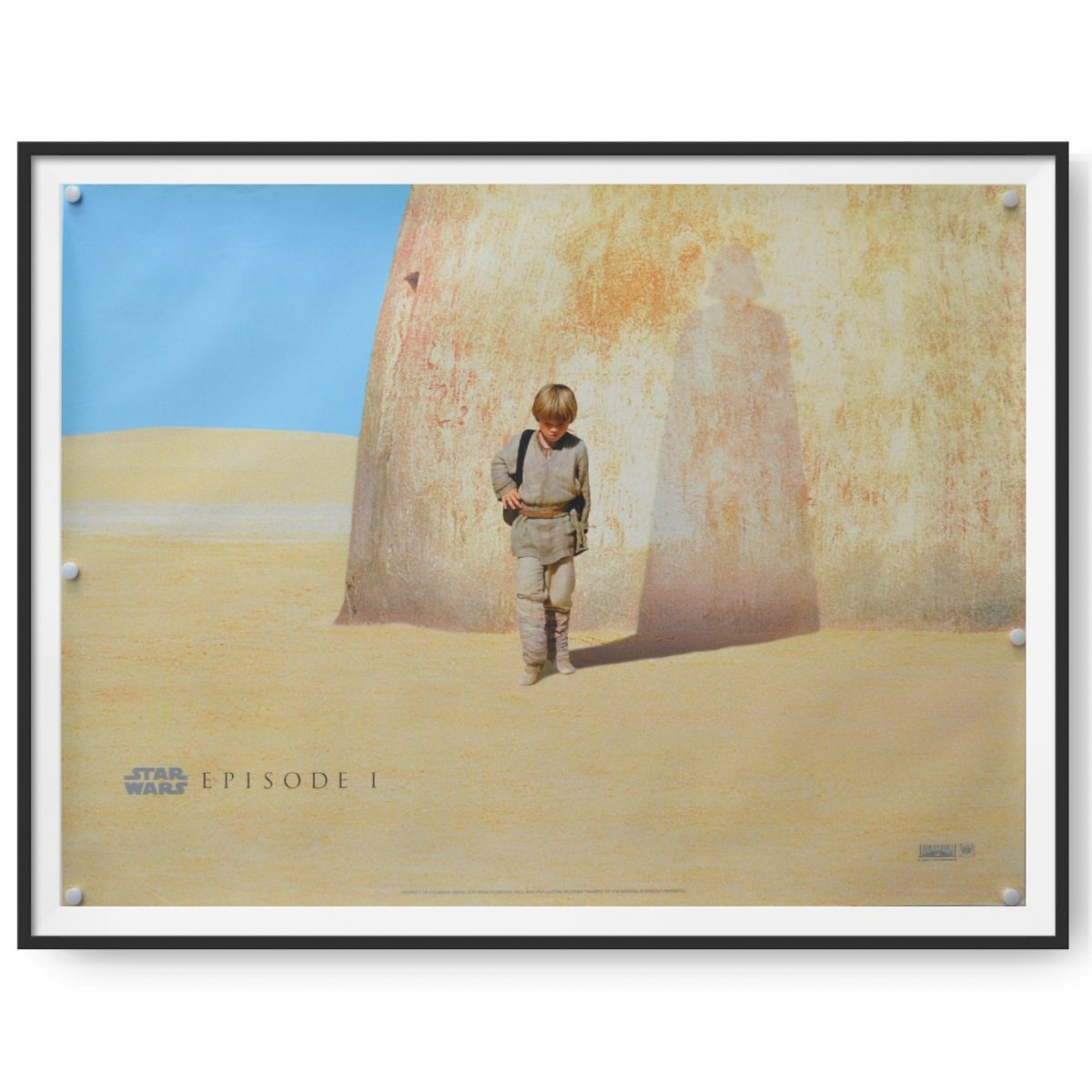 This a framed UK quad poster for the 1999 release of Episode 1 of the Star Wars series. A shadow on the sandstone rock suggest who Anakin Skywalker is set to become.