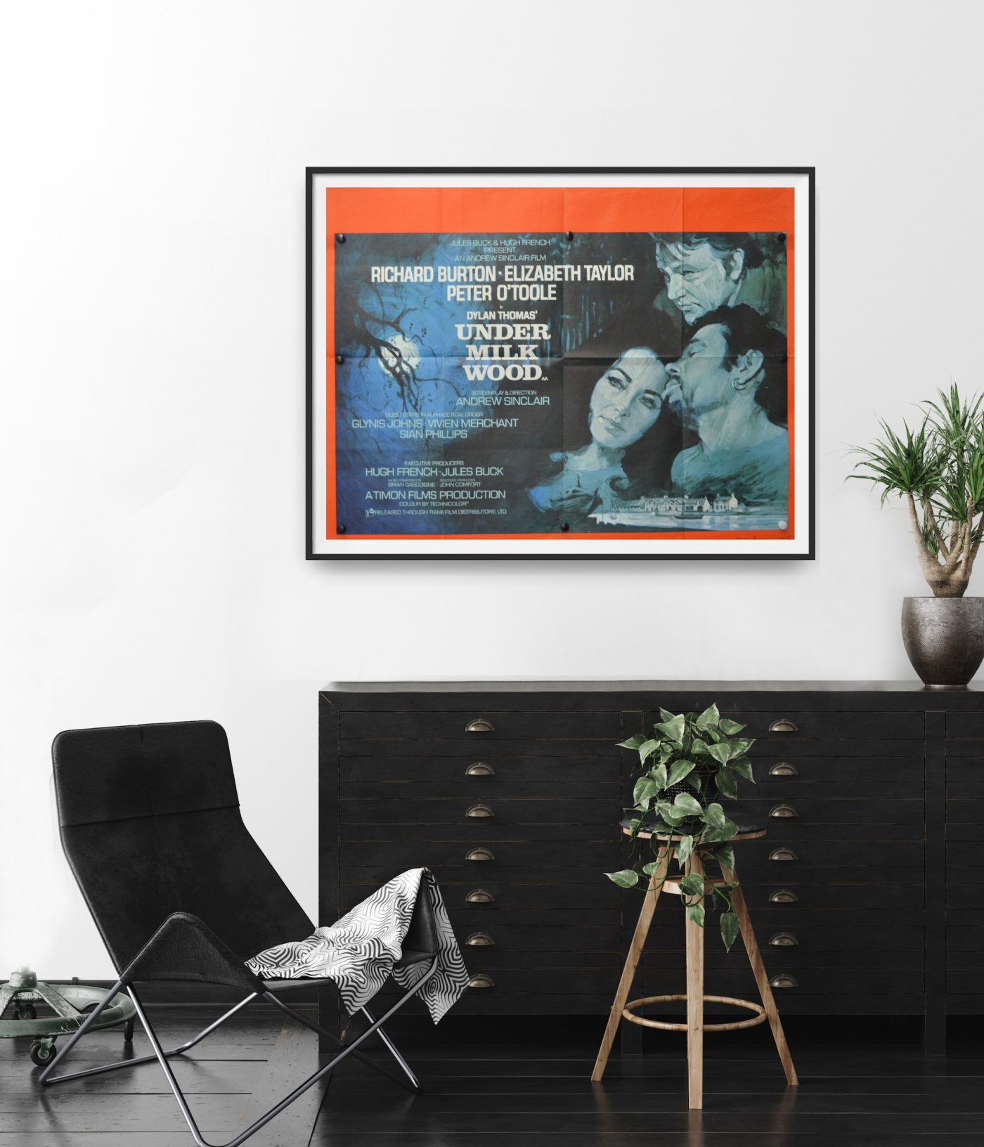 This poster for the film 'Under Milk Wood' shows a painting of Richard Harris, Peter O'Toole and Elizabeth Taylor. The picture is hung in a room for scalee.